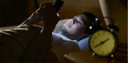 young man using a smartphone in his bed at night picture id