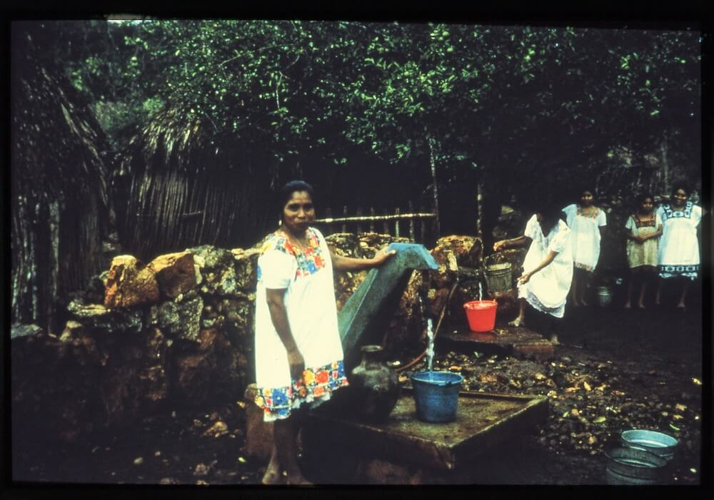 maya women getting water from gas powered pump compressed