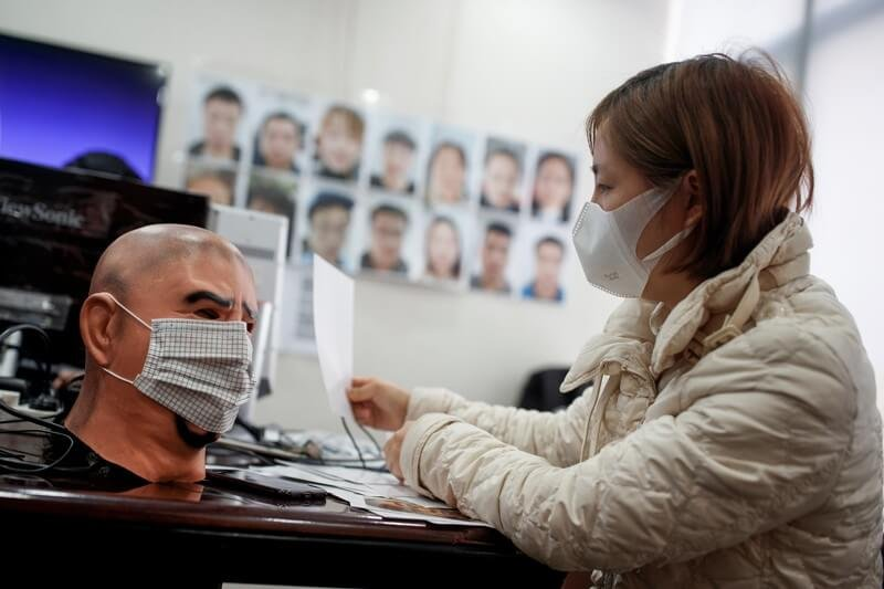 A software engineer at Hanwang Technology in Beijing tests a facial-recognition programme that identifies people wearing face masks. Credit: Thomas Peter/Reuters