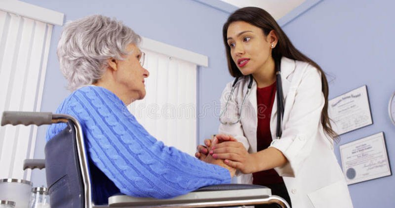 hispanic woman doctor comforting disabled elderly patient mexican women