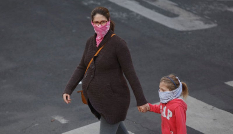 pregnant woman and child walk with masks during covid outbreak x