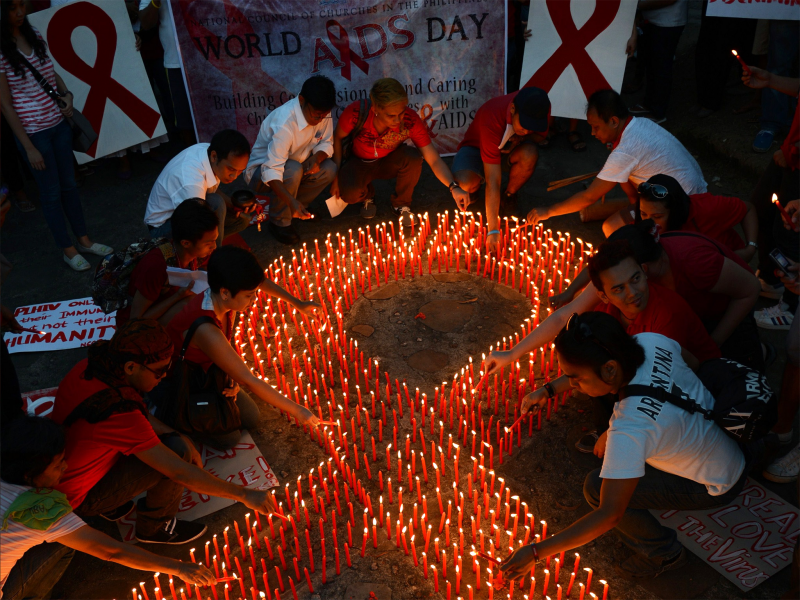 Activists light candles on World Aids Day in Manila. Credit: Getty Images