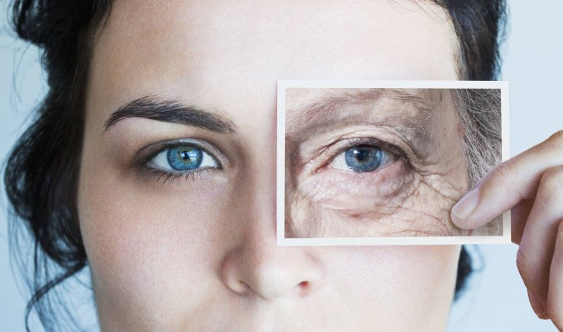 young woman with photo of aged eye over her high res stock photography